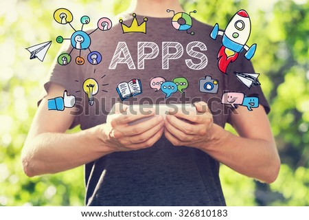 APPS concept with young man holding his smartphone outside in the park toward sunset - stock photo