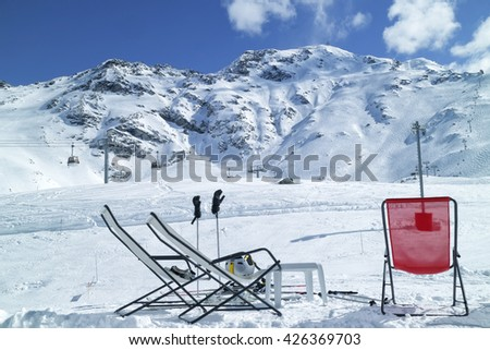 Apres ski at high Alps mountains winter resort of Les Arcs. Red and white relaxing lounge chairs on snow in front of ski slopes and lifts.  - stock photo