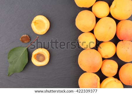 Apricots. Group of harvested apricots on a basket, top view, Blackboard background. - stock photo