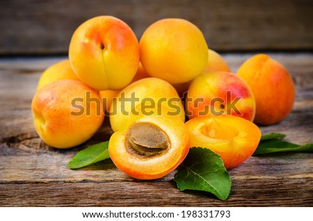 apricots on a dark wood background. toning. selective focus on apricots with a stone. - stock photo