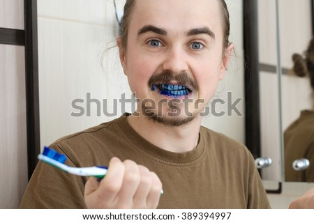 April Fools  joke, confused man about colored tooth brush - stock photo