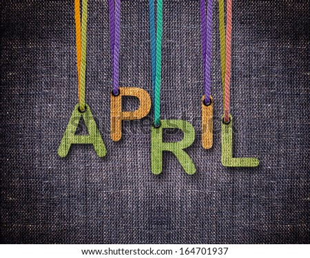 April letters hanging strings with blue sackcloth background. - stock photo