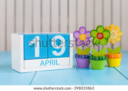 April 19th. Image of april 19 wooden color calendar on white background with flowers. Spring day, empty space for text. The Day Of Snowdrop - stock photo