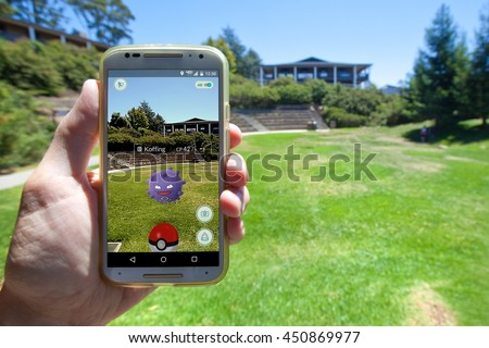 "APTOS, CALIFORNIA - JULY 11, 2016: The hit augmented reality smartphone app ""Pokemon GO"" shows a Pokemon encounter overlain on a college campus in the real world. - stock photo"