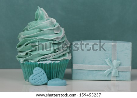 Aqua cupcake with presents and candy hearts - stock photo