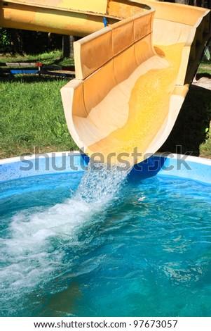 Aqua park yellow water slide. - stock photo