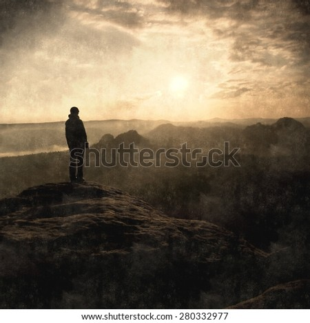 Aquarelle, Watercolor paint. Silhouette of young tourist with hands in pockets. Sunny spring daybreak in rocky mountains. Girl stand on rocky view point above misty valley. Painting effect. - stock photo