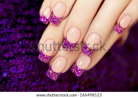 Aquarium nail with blue chips and gold sequins in female hands. - stock photo