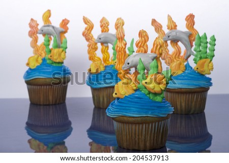 Aquatic under the sea themed cup cakes created at home with royal icing coral and sea weed marshmallow fondant dolphins and fish. Perfect for summer parties - stock photo