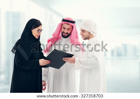 Arab business people in a meeting, three business people standing in a modern office interior discussing work, ethnic business people, business team. - stock photo