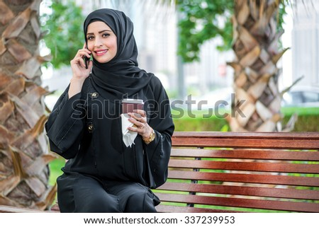 Arab coffee and phone. Arab businesswomen in hijab holding coffee on the street and talking on cell phone on the background of skyscrapers  and looking at camera. woman is dressed in a black abaya - stock photo