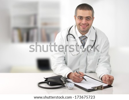 Arab doctor in his office writing notes in his office. - stock photo
