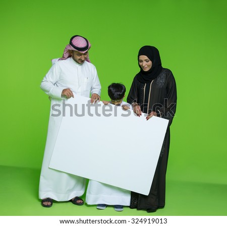 Arab family holding blank placard - stock photo