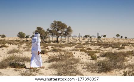 Arab man in national dress in desert - stock photo