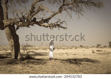 Arab man in national dress stands in the desert and looks at the city of Dubai - stock photo