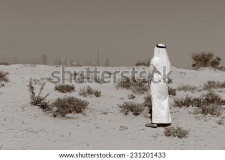 Arab man in national dress stands in the desert and looks at the city of Dubai. Toned. - stock photo