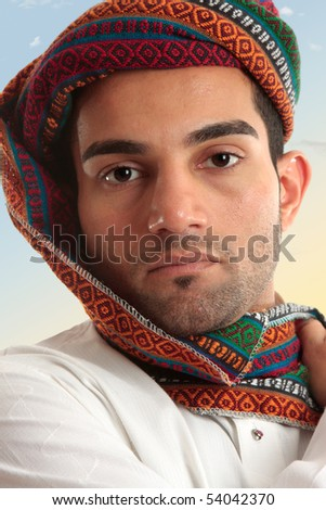 Arab man wearing a colourful wovan turban style  head piece.  These  serve a purpose of protecting nose and mouth from dust and sand storms as the fabric can be wrapped across the face when needed. - stock photo