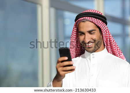 Arab saudi businessman working  with his phone with an office building in the background            - stock photo
