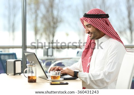 Arab saudi man working online with a laptop and smartwatch in a coffee shop or an hotel bar with a window and outdoor terrace in the background - stock photo