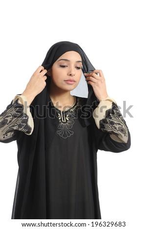 Arab saudi woman dressing putting headscarf isolated on a white background   - stock photo