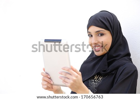 Arab woman holding a tablet and looking at camera on a white wall background         - stock photo