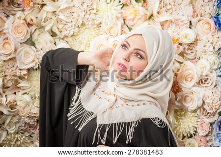 Arab woman in a burqa looks with hope. . fresh flowers in the background - stock photo