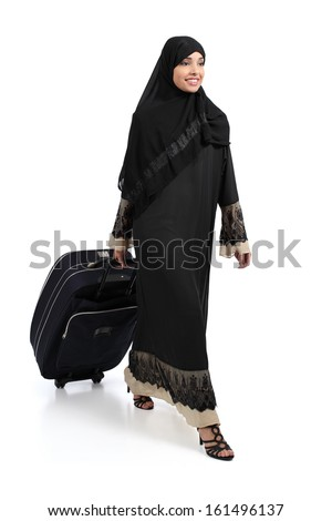 Arab woman walking carrying a suitcase isolated on a white background              - stock photo