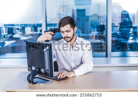 arabian asian beard young adult  businessman with black metal gun near temple head against window glass reflection in office room space look pc computer monitor watch bad sad information - stock photo