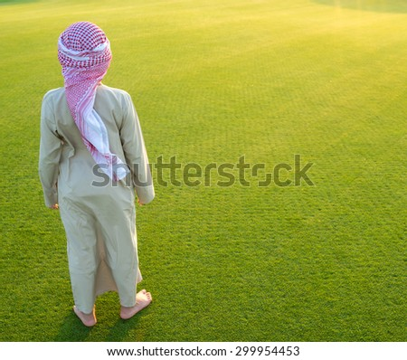 Arabian boy on grass meadow - stock photo