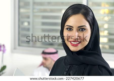 Arabian Businesswoman wearing hijab with her boss in background, Arabian businesspeople in office - stock photo