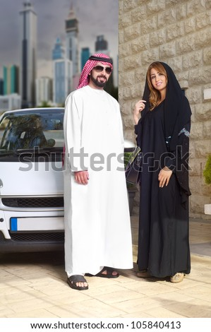 arabian couple against their car posing at home with cityscape behind - stock photo