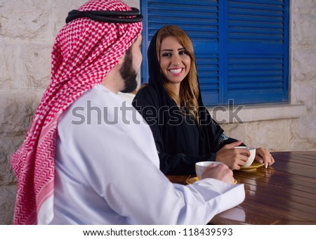arabian couple relaxing in the garden drinking tea - stock photo
