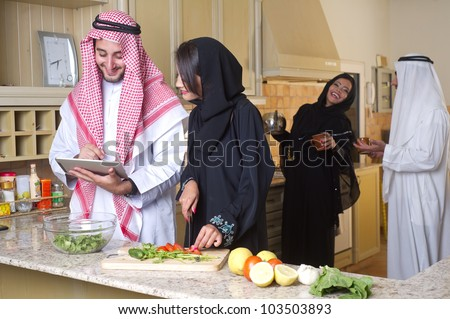 arabian couples gathering cooking & drinking coffee in kitchen - stock photo