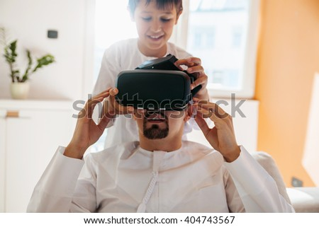 Arabian Father And Son Using VR Headset At Home - stock photo