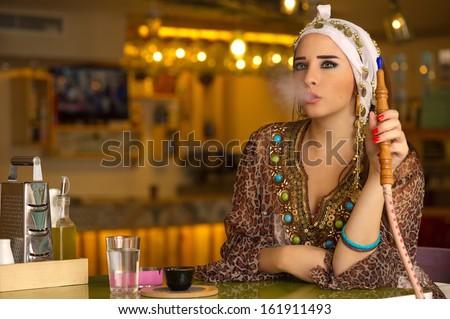 Arabian girl holding the hookah pipe in a coffee shop - stock photo