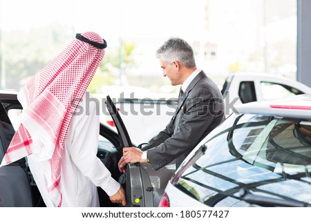 Arabian man getting in a new car for test drive at vehicle dealership - stock photo