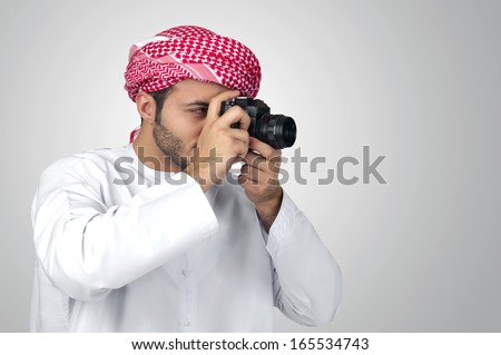 Arabian photographer taking pictures isolated - stock photo