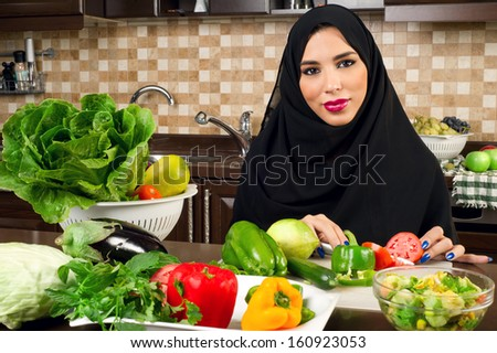 Arabian woman preparing salad in the kitchen - stock photo