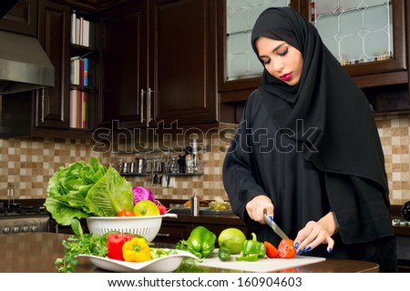 Arabian woman wearing hijab cutting veggies in the kitchen - stock photo