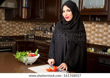 Arabian woman wearing hijab cutting veggies in the kitchen - stock photo