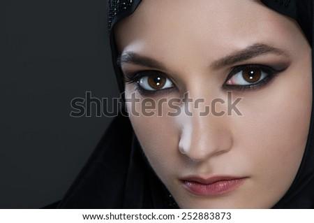 arabian woman with black veil on black background - studio shot - stock photo