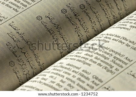 Arabic and English passage in Koran (Qur'an) - stock photo
