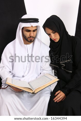 Arabic Couple Referring To The Holy Quran - stock photo