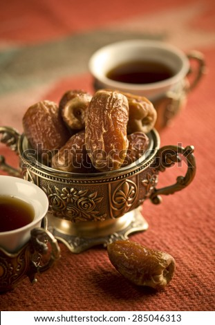 Arabic dates in an ornamental bowl and tea cups. Arabain refreshment. - stock photo