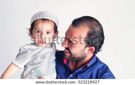 Arabic Father playing with his son - stock photo