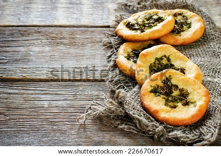 Arabic flat bread with herbs on a dark wood background. tinting. selective focus on the greens - stock photo
