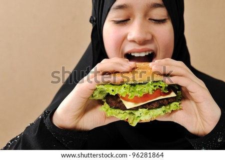 Arabic girl eating burger - stock photo
