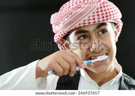 Arabic kid brushing teeth - stock photo