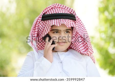 Arabic kid talking on phone - stock photo