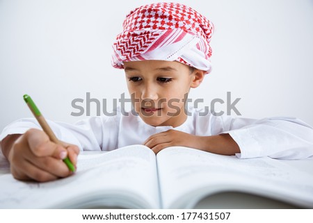 Arabic little boy reading and doing homework - stock photo